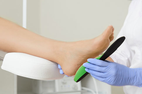 Doctor fitting a foot with orthodics