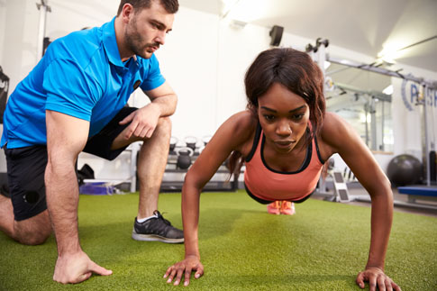Women doing a push up with a trainer